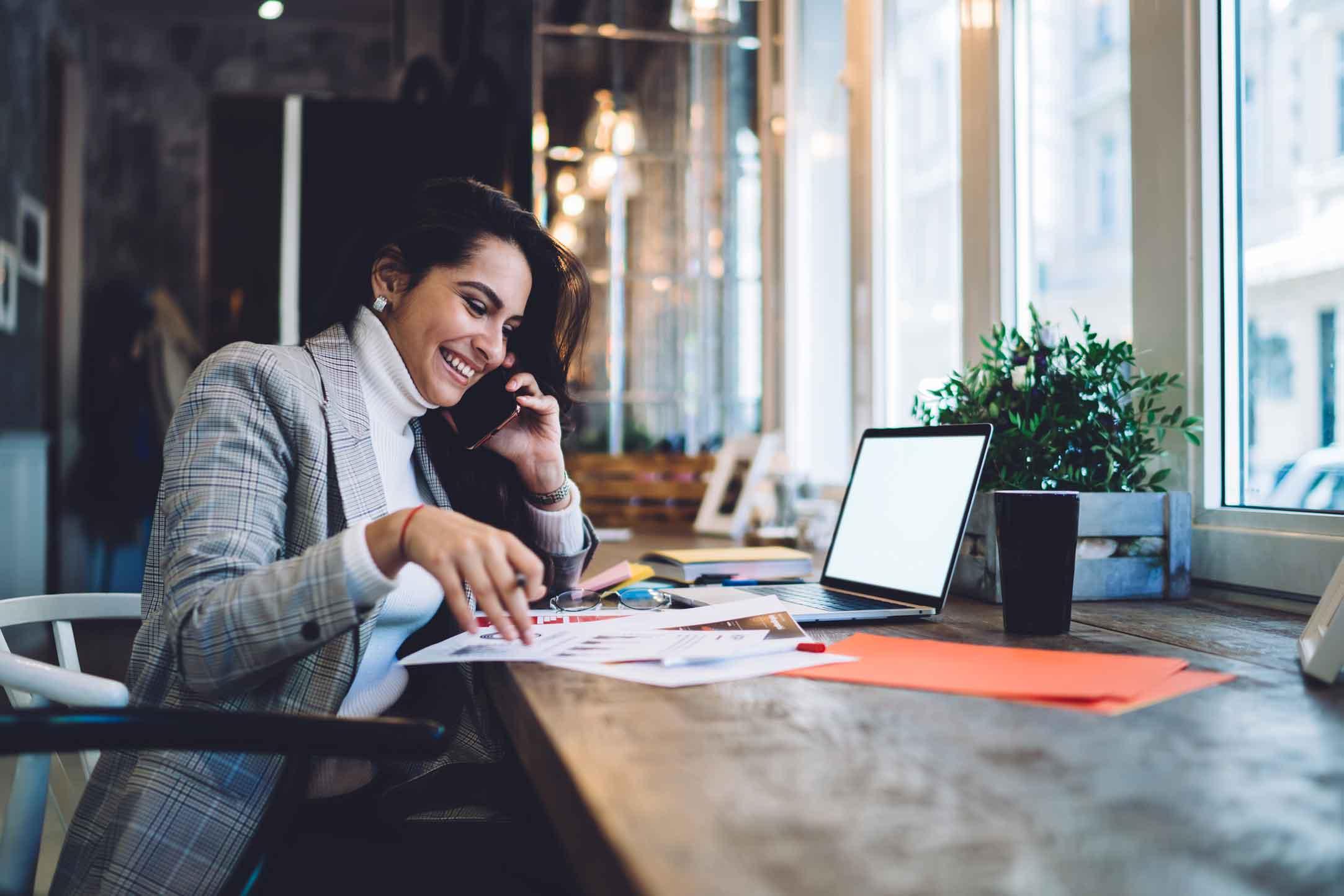 fille souriante au téléphone à son bureau